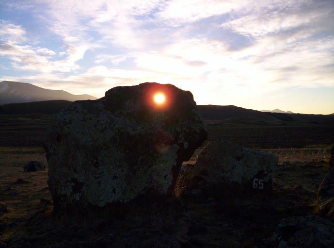 Há furos nas rochas. A imagem mostra uma rocha alinhada com o Sol.